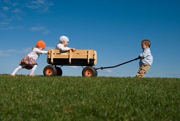 Three Children Pushing, Pulling, and Playing with Wagon stock photo