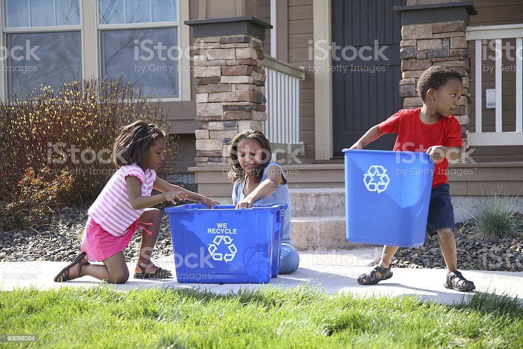 Three children putting items into recycle bin royalty-free stock photo