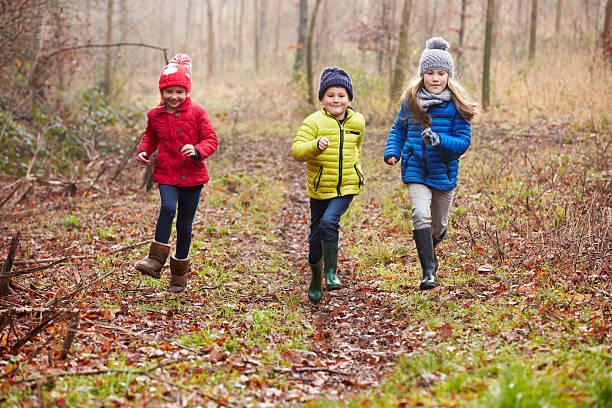 three children running through winter woodland - bos spelen stockfoto's en -beelden