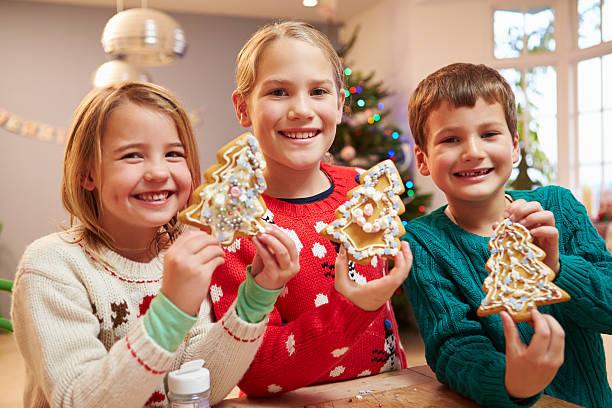 drei kinder zeigen die weihnachtsplätzchen - weihnachten 7 jährige stock-fotos und bilder
