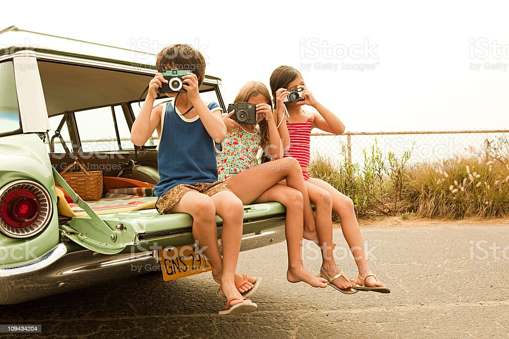 Three children sitting on back of estate car taking photographs stock photo