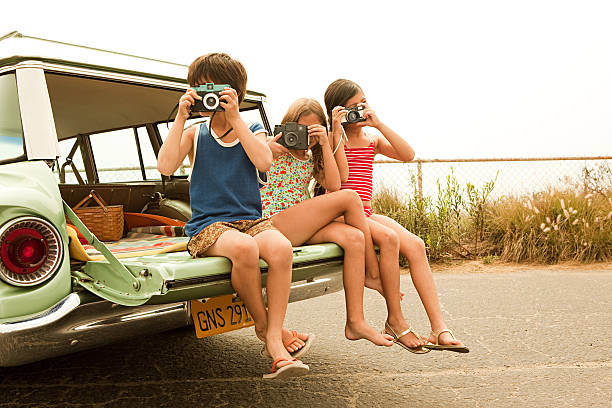three children sitting on back of estate car taking photographs - family pictures 個照片及圖片檔