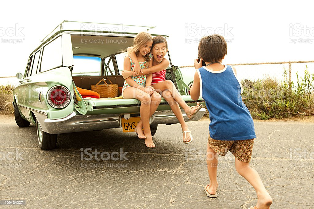 Three children sitting on back of estate car taking photographs royalty-free stock photo