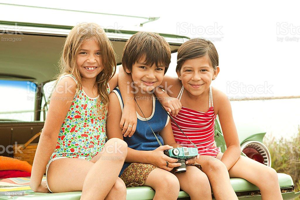 Three children sitting on back of estate car wearing swimwear royalty-free stock photo
