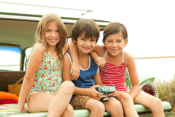 Three children sitting on back of estate car wearing swimwear stock photo