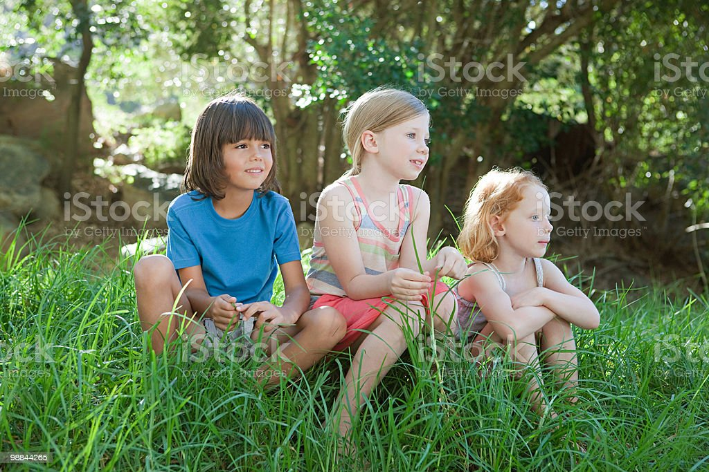 Three children sitting on grass foto royalty-free