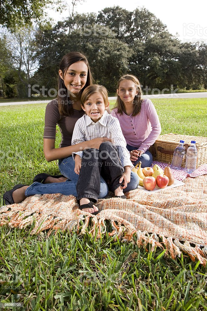 Three children sitting on picnic blanket in park royalty-free stock photo