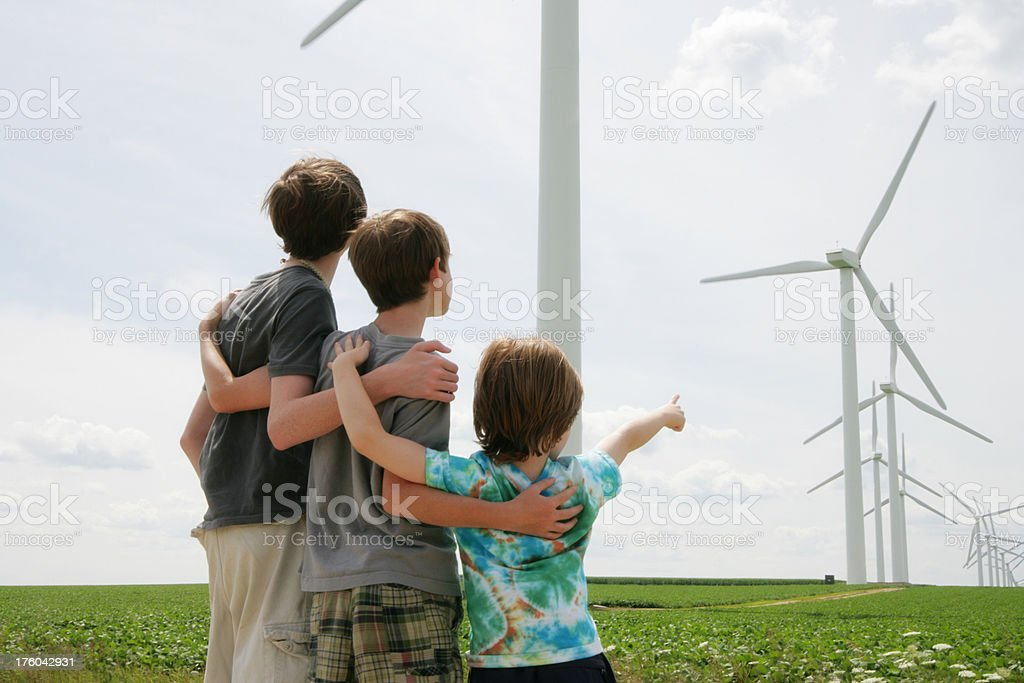 Three Children Standing Together Looking at Wind Turbines- Renewable Energy stock photo