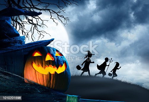A jack o lantern, a witch's hat, and a broom stick, sit in front of three trick or treating children silhouetted against a cloudy moonlit sky on Halloween night.