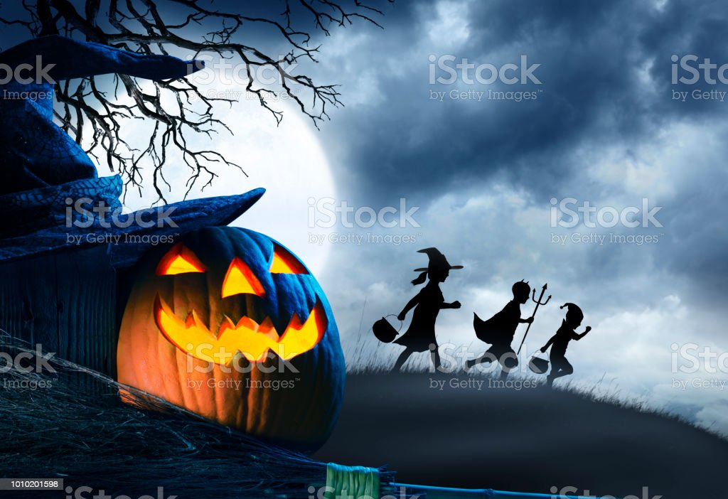 Three Children Trick Or Treating Silhouetted Against Moonlit Sky stock photo