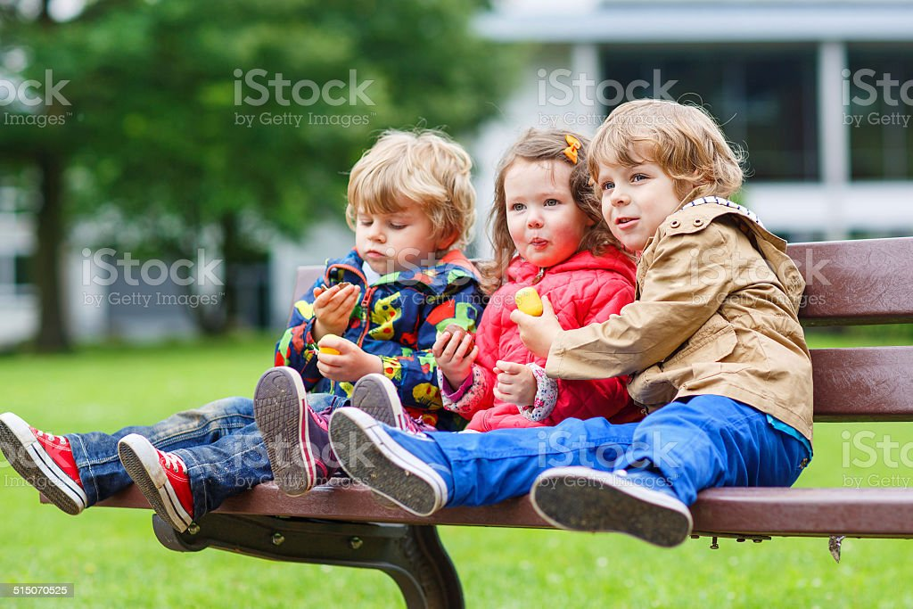 Three children: two little brothers and one sister hugging stock photo