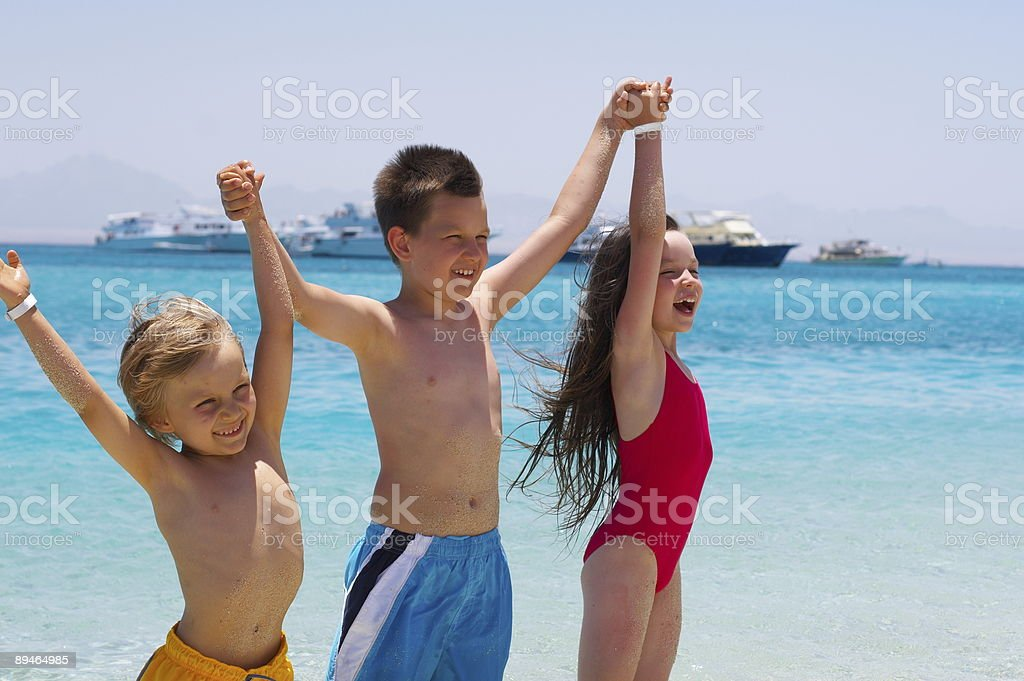 Three Children Wading in Ocean royalty-free stock photo