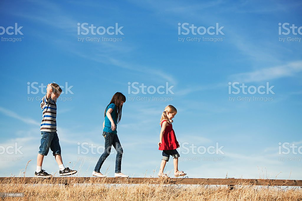 Three children walking along wooden fence stock photo
