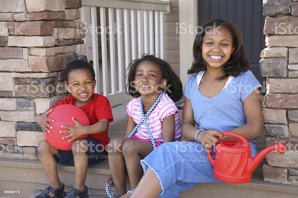 Three children with toys on porch royalty-free stock photo