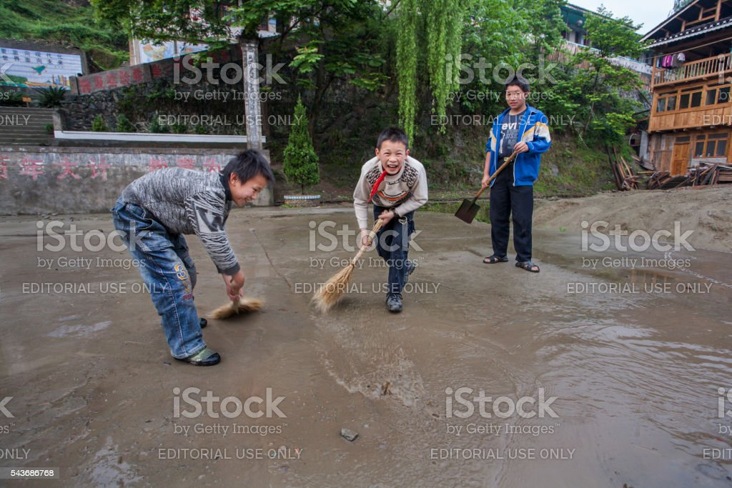 Three Chinese rural schoolboys sweep the school grounds laughing stock photo