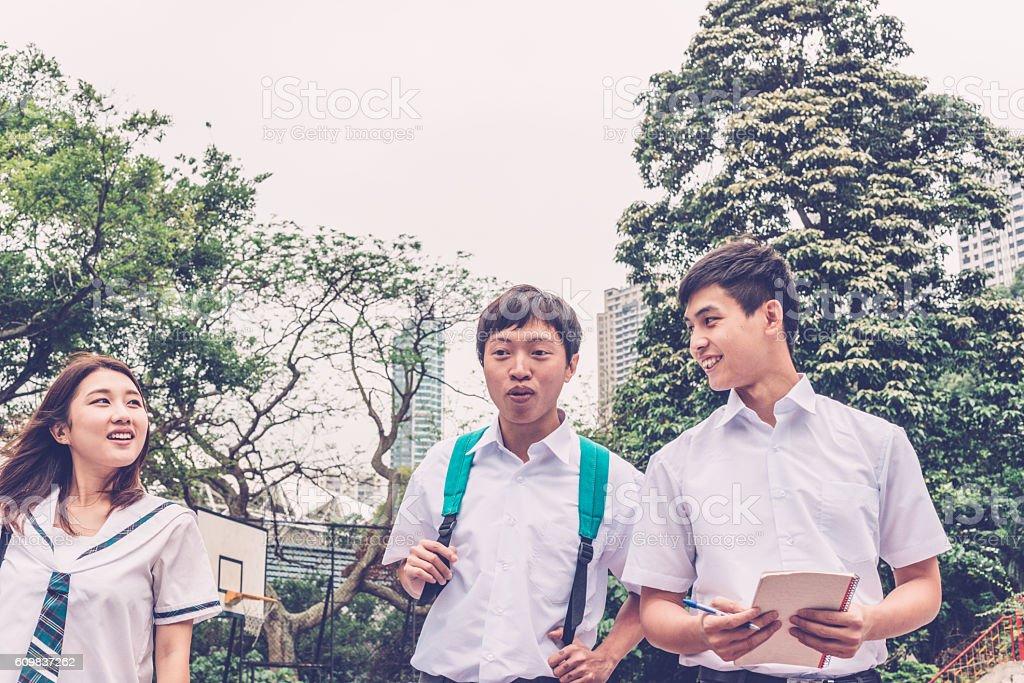 Three Chinese Students Walking on Basketball Ground, Hong Kong, China stock photo