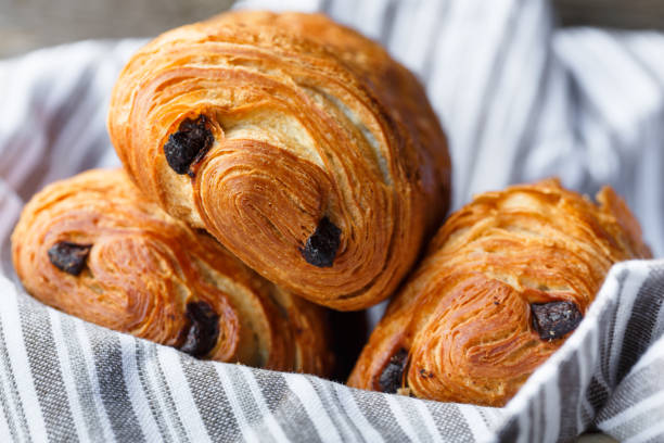 three chocolate bread three pain au chocolat in a bread basket pastry dough stock pictures, royalty-free photos & images