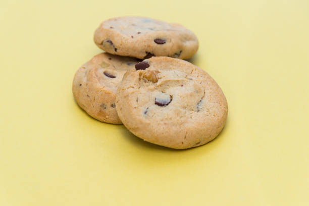 Three chocolate chip cookies isolated on light yellow background stock photo