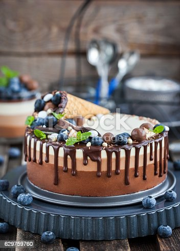 480972628 istock photo Three chocolate mousse cake decorated with waffle cone, fresh bl 629759760