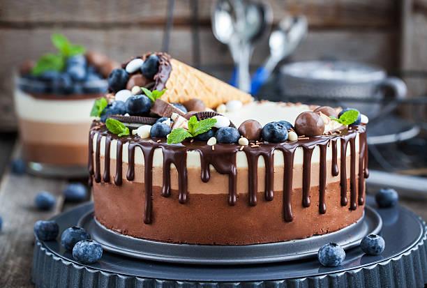 three chocolate mousse cake decorated with waffle cone, fresh bl - käsekuchen kekse stock-fotos und bilder