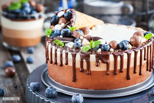 480972628 istock photo Three chocolate mousse cake decorated with waffle cone, fresh bl 638596276