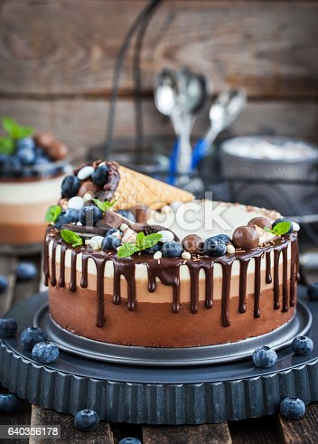 480972628 istock photo Three chocolate mousse cake decorated with waffle cone, fresh bl 640356178