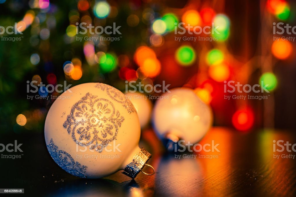 Three Christmas balls on a blurred festive background a garland of New Year's lights stock photo