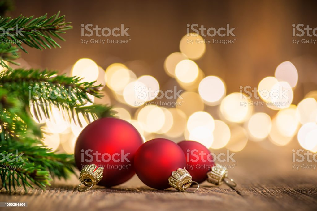 Three Christmas Balls on rustic wood and sparkles defocused lights on the backgorund stock photo