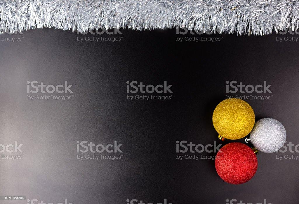 Drei Christbaumkugeln liegt auf einem schwarzen Hintergrund mit schwachem Licht mit Silber Flitter, Weihnachtsschmuck. – Foto