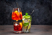 Three classic cocktail glasses on wooden table. Negroni, Spritz and mojito. With copy space