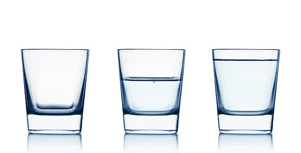 Three clear glasses with different amounts of water in them stock photo