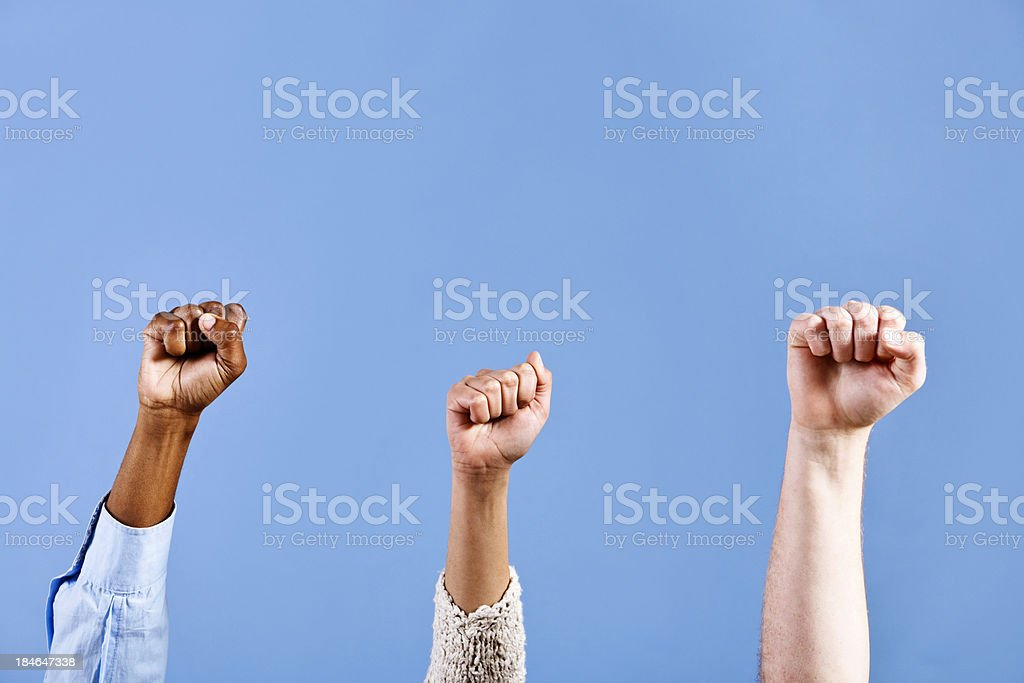 Three clenched fists being brandished against sky blue - power! stock photo