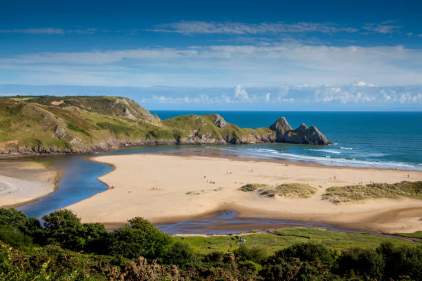 Three Cliffs Bay, Wales Three Cliffs Bay on the Gower Peninsular, West Glamorgan, Wales, UK, which is a popular Welsh coastline attraction of outstanding beauty bay of water stock pictures, royalty-free photos & images