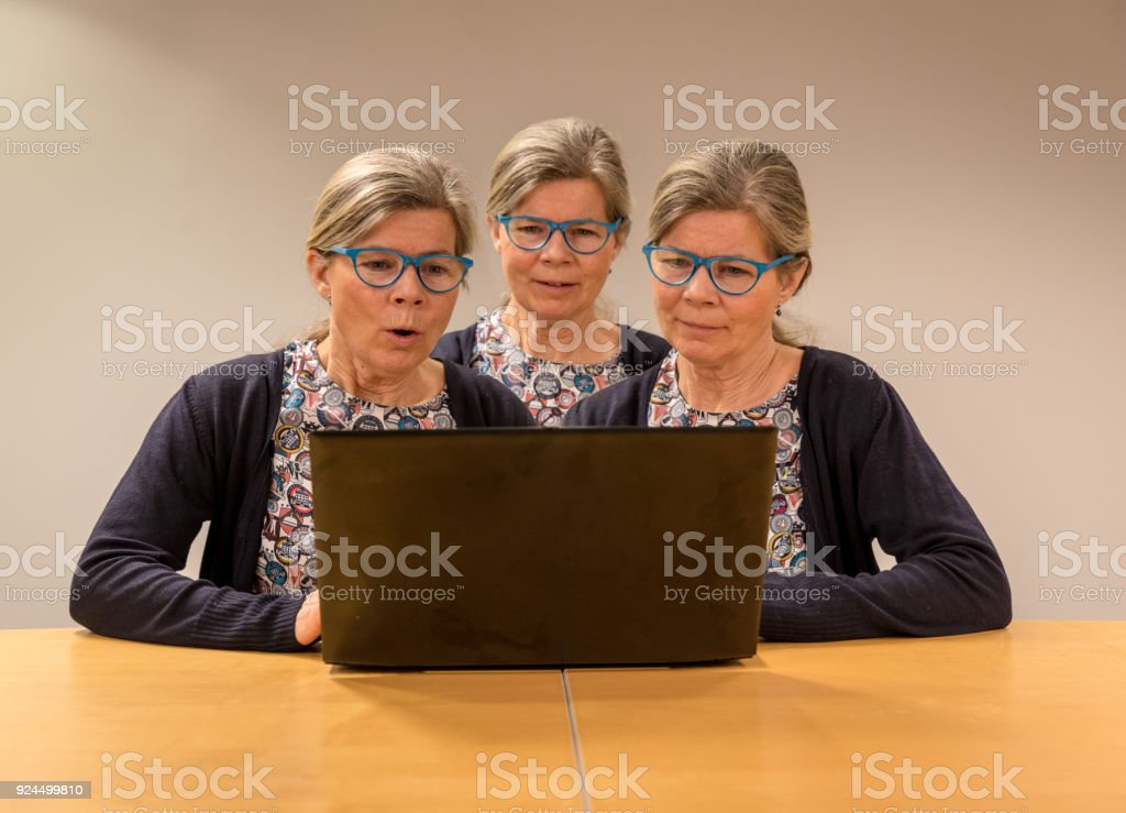 Three clones of one woman with glasses working with a pc. stock photo