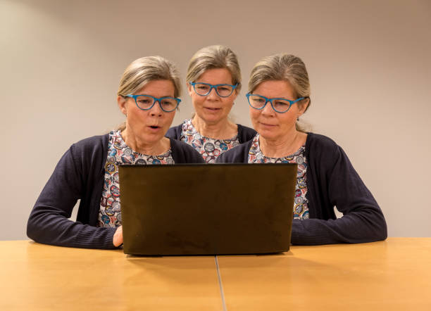 three clones of one woman with glasses working with a pc. - triplets stock photos and pictures