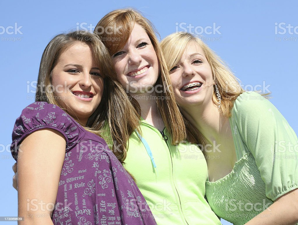 three close friends hugging and smiling royalty-free stock photo