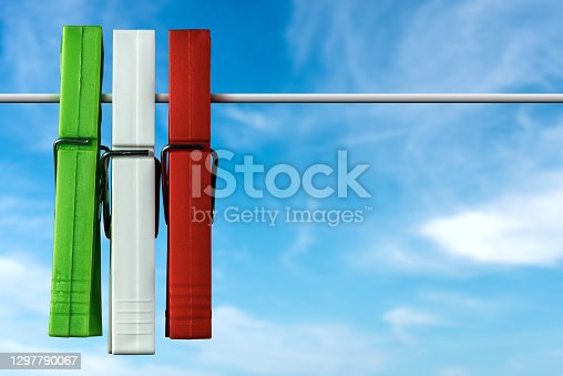 Closeup of three clothespins with the colors of the Italian flag on a blue sky with clouds and copy space.