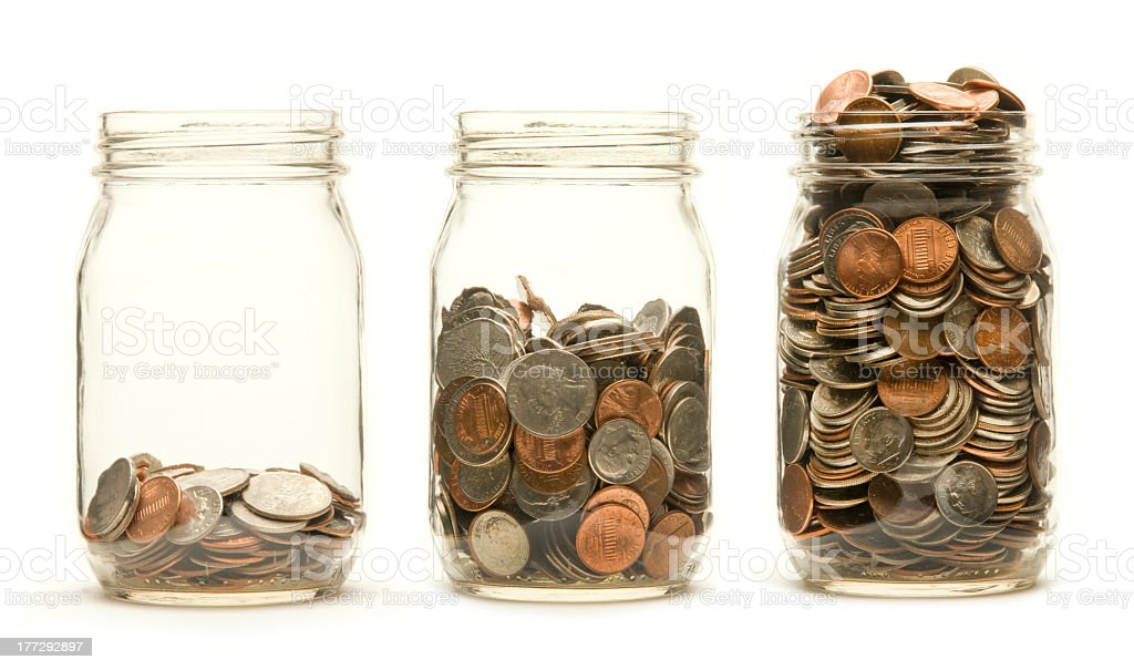 Three coin savings jars each fuller than the last stock photo