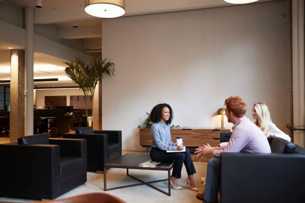 drei kollegen auf eine gelegenheitsarbeit sitzung in einem lounge-bereich - lässiges wohnzimmer stock-fotos und bilder