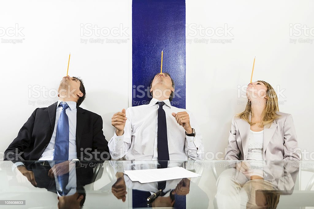Three colleagues balancing pencils on their  noses royalty-free stock photo