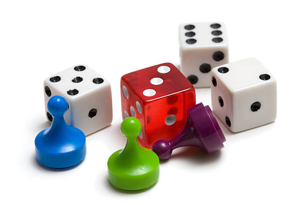 Three colored game pieces and four dice on white background stock photo