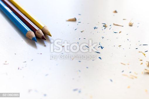 Colored pencils lying on a white surface with pencil shavings scattered around them.