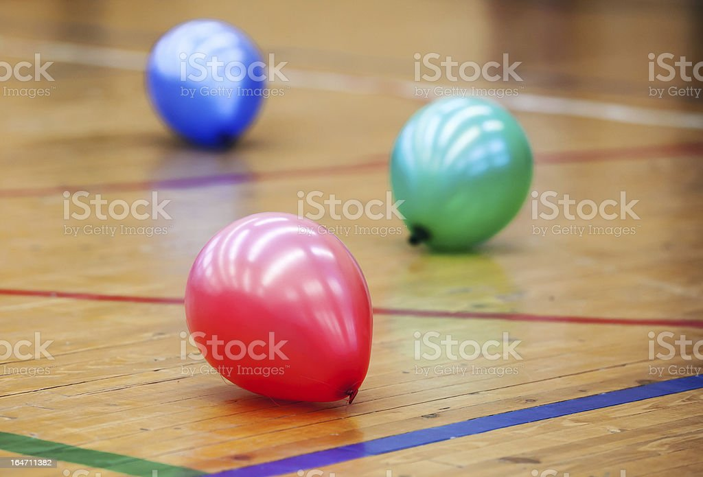 Three colorful balloons on wooden floor of sports hall royalty-free stock photo