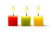 Three colorful cube candles in a row on white