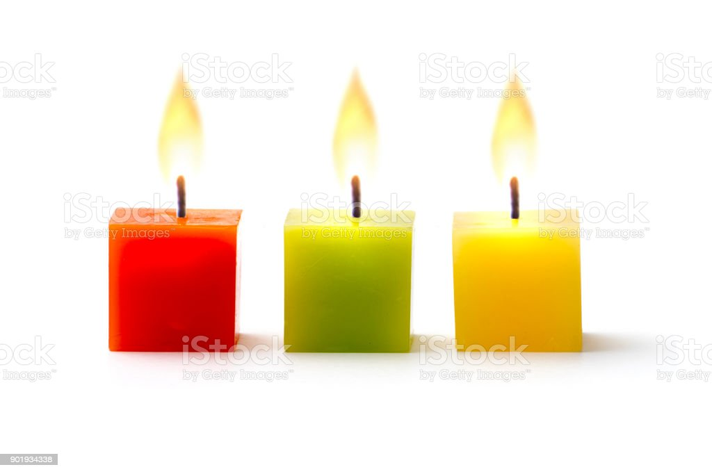 Three colorful cube candles in a row on white stock photo
