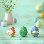 Three colorful Easter eggs on green wood