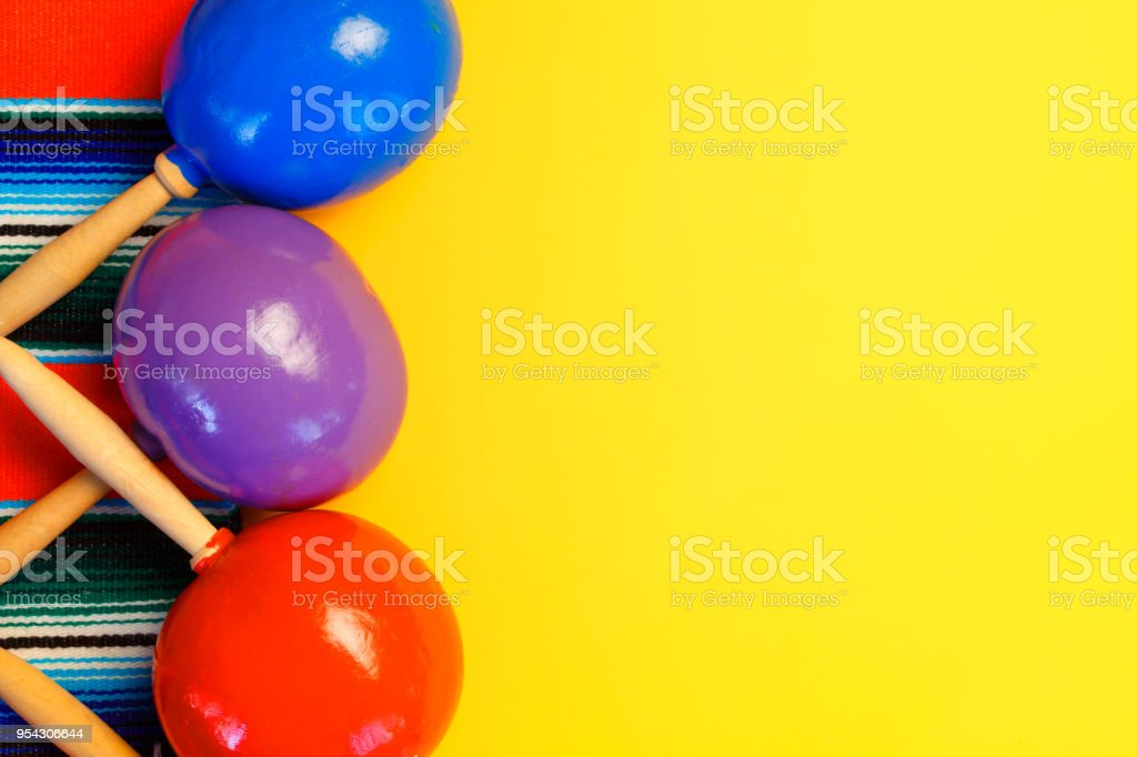 three colorful maracas resting on traditional mexican blanket stock