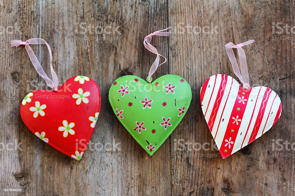 Three colorful metal hearts on a wooden background stock photo