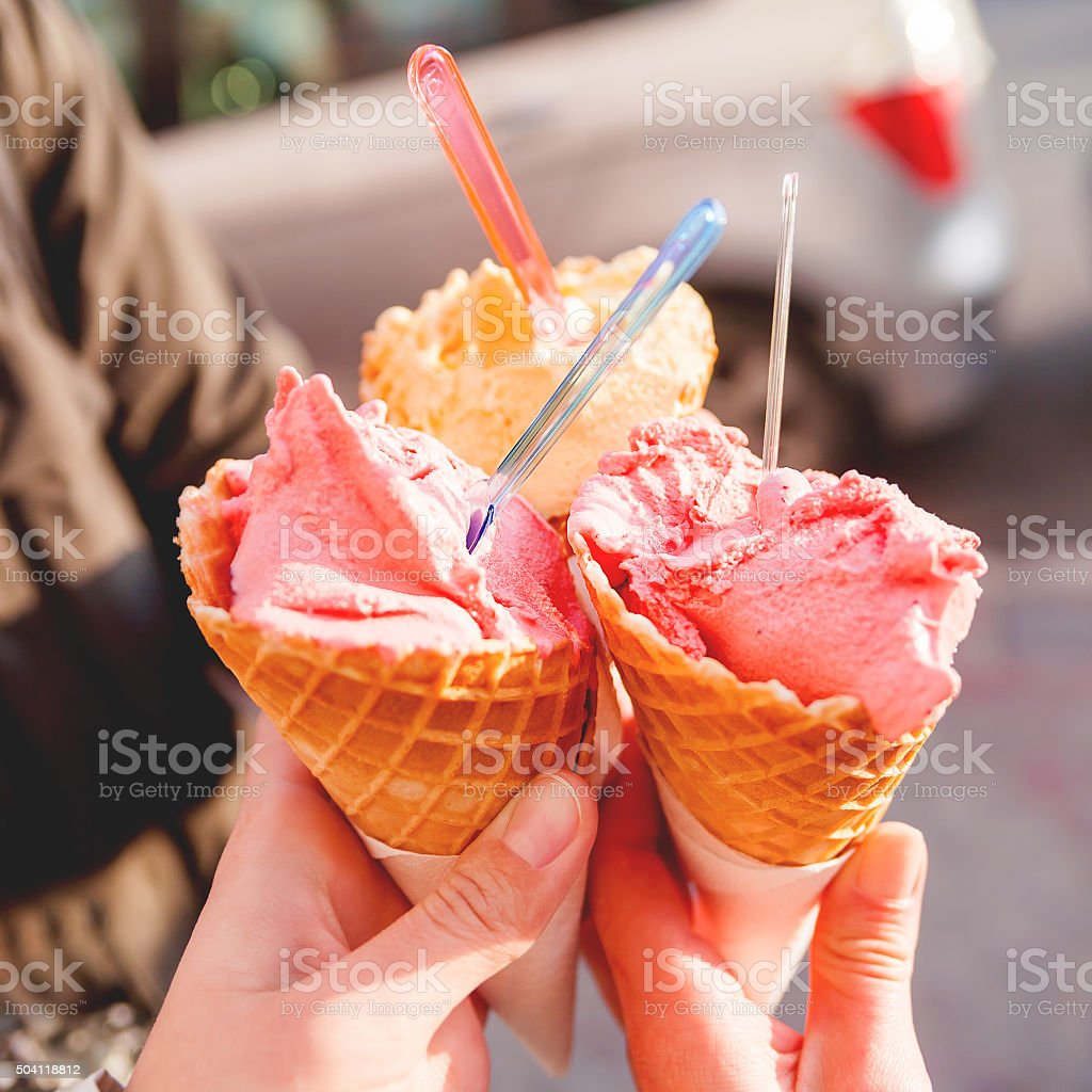 Three colorful tasty ice cream cones in hands. stock photo