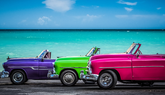 Three colorfully convertible classic cars parked before the Caribbean Sea on the Malecon in Havana Cuba